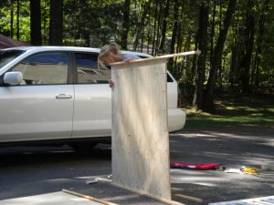 a woman holding up a piece of plywood