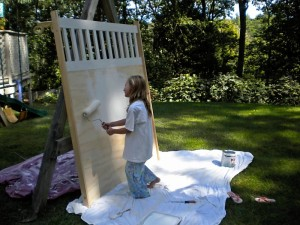 a little girl painting a pice of plywood