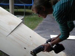 a woman cutting a large piece of plywood
