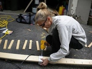 a woman drilling a piece of wood
