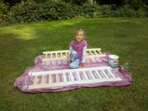 A little girl painting railings