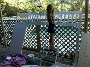 A little girl painting a bed frame white