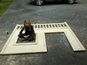 a little girl sitting on a driveway on a piece of plywood