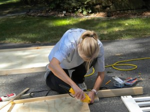 a woman drilling into wood frame