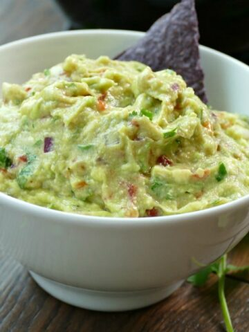 A close up of a bowl of Guacamole with a blue chip