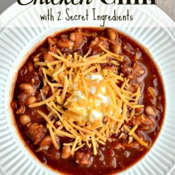 A close up of a bowl of chicken chili topped with cheese