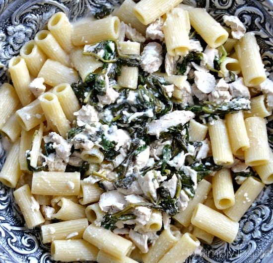 a bowl of penne pasta with chicken and cooked spinach mixture