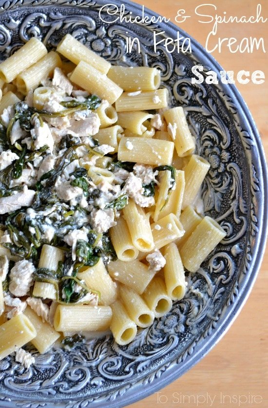 closeup of a chicken and spinach mixture over penne pasta in a silver bowl