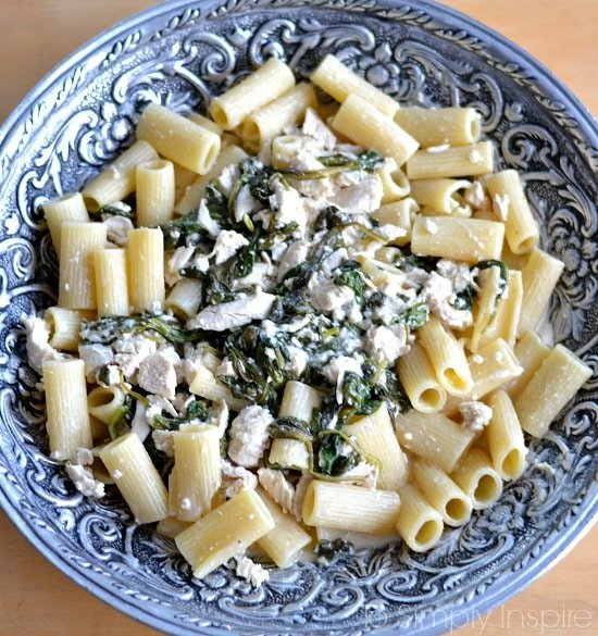 A bowl of pasta with spinach chicken feta sauce in a big silver serving bowl