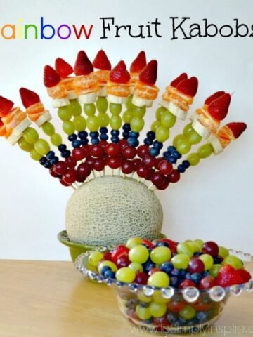 Fruit kabobs with grapes blueberries, oranges strawberries wit a bowl of fruit in front
