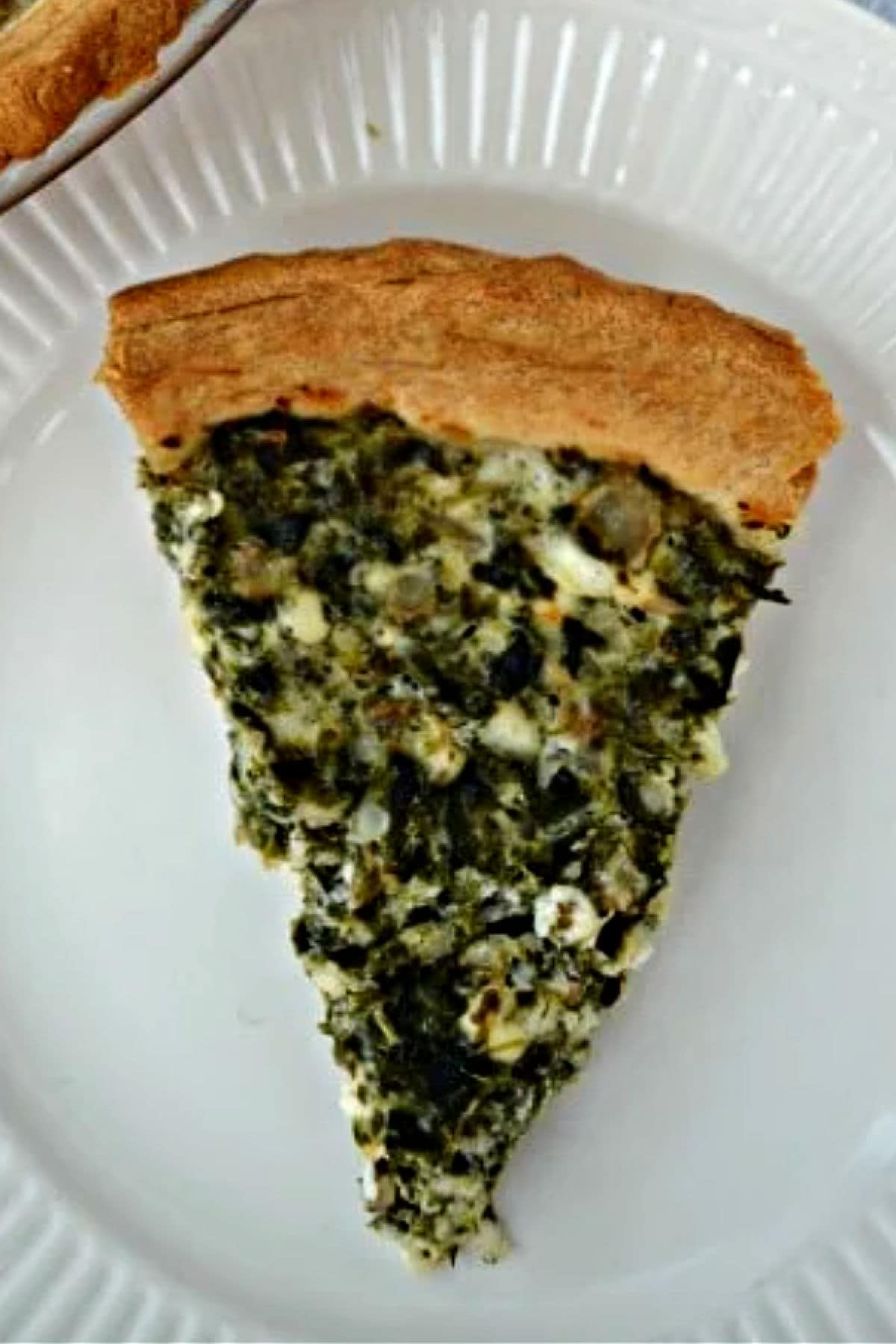 Slice of Spinach Pie on a white plate with whole spinach pie in the background