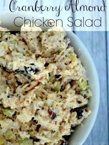 a white bowl full of chicken salad with cranberries