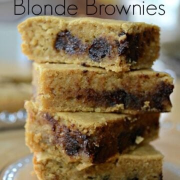 four blonde brownies with chocolate chips stack on a plate