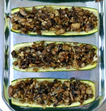 three hollowed out zucchini halves filled with sautéed mushrooms on a silver plate