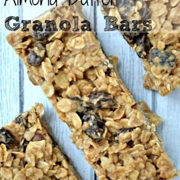 three granola bars with raisins on a grey wood table