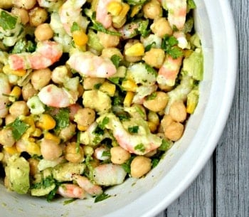 shrimp, chickpea, avocado and corn salad in a white bowl