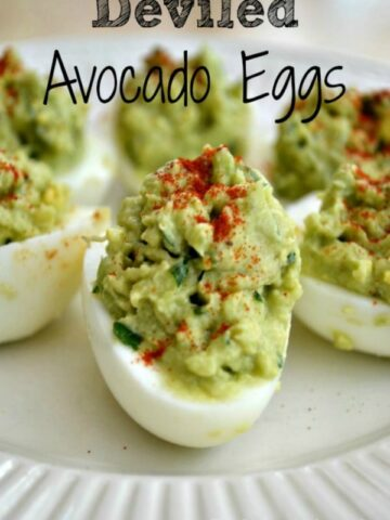 A close up of a white plate with Avocado Deviled Eggs