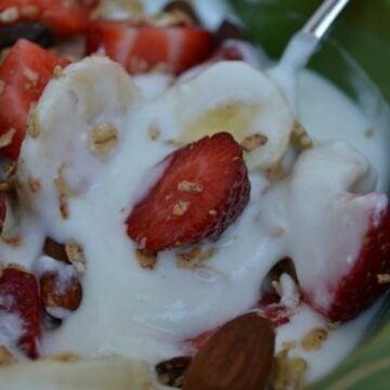 a green bowl of vanilla yogurt with strawberries and bananas