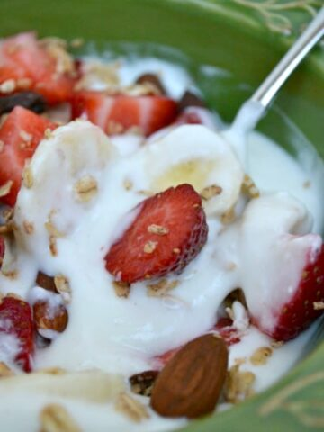 a green bowlful of greek yogurt with bananas and strawberries
