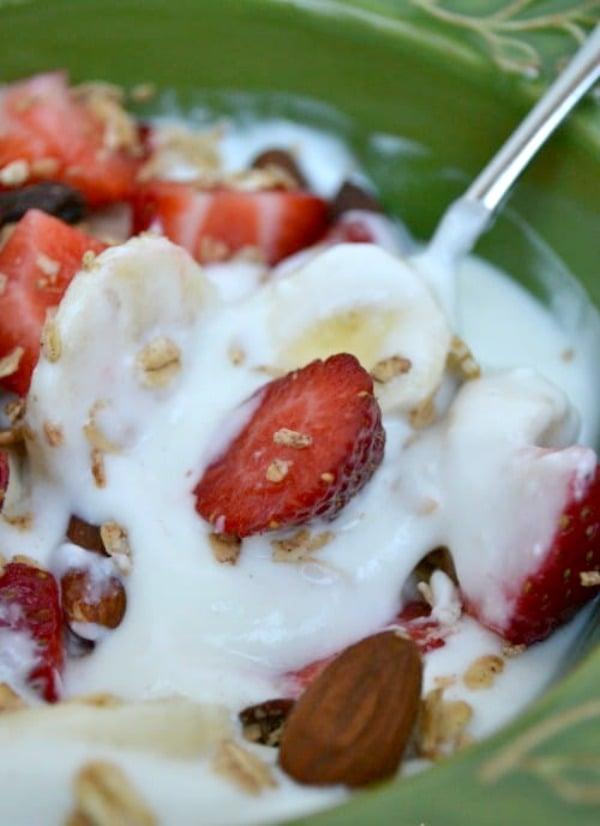 a green bowlful of greek yogurt with bananas and strawberries