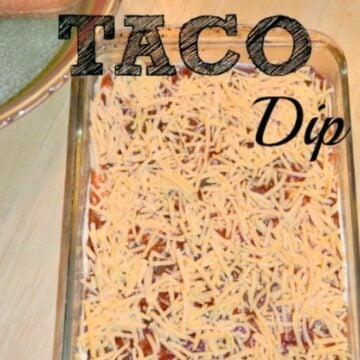 closeup of taco dip topped with shredded cheese in a rectangle glass dish