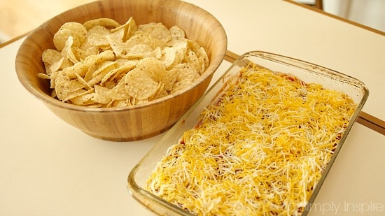 Layered taco dip recipe in a serving dish beside a bowl of tortilla chips.