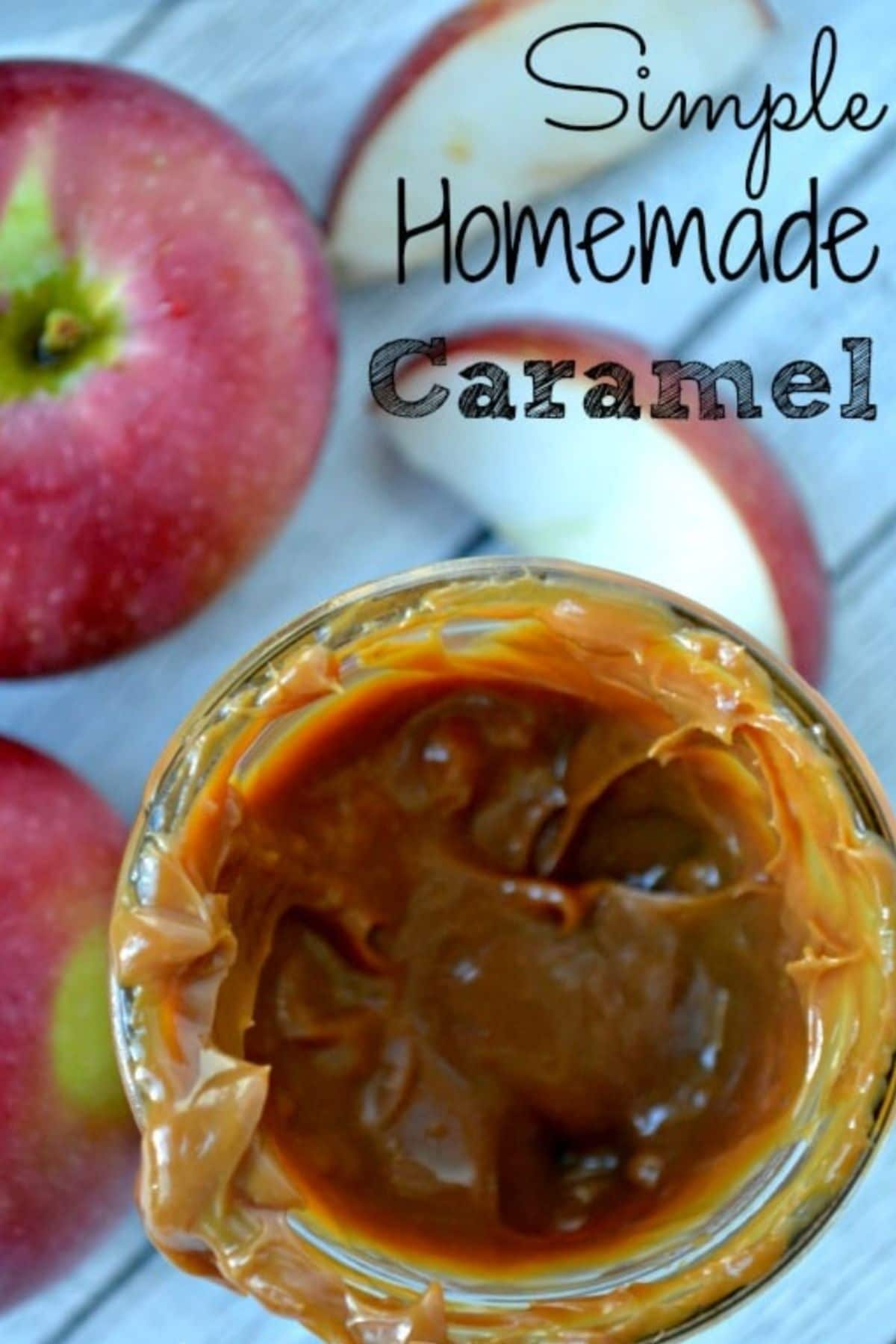 Homemade caramel sauce in a jar surrounded by apples