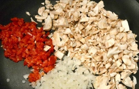 diced onions, mushrooms and red peppers in a pan