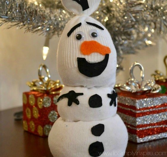 olaf sock snowman on a wood table in from of a small silver christmas tree