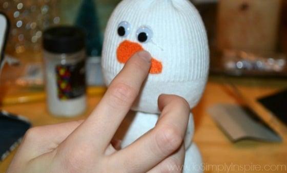 a girls hand placing a felt carrot nose on a sock snowman craft