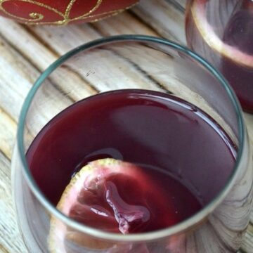 a stemless wine glass with red wine wassail and a lemon slice