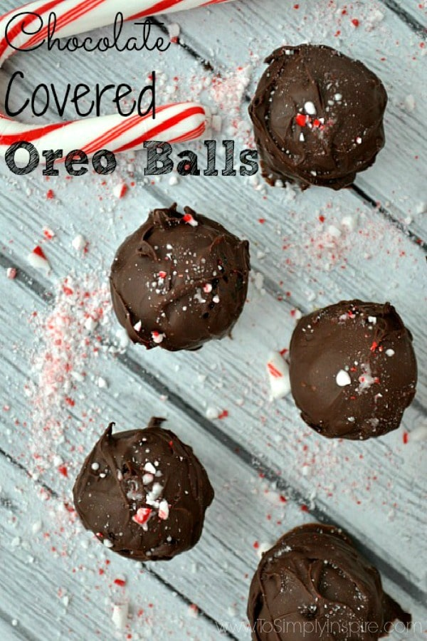 Oreo Cookie Balls on a gray background sprinkled with crushed candy canes.