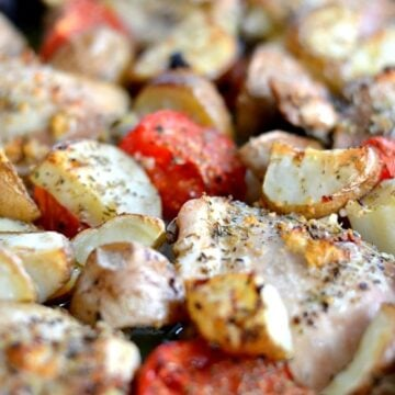 A close up of roasted Chicken thighs, tomatoes, potatoes and onions