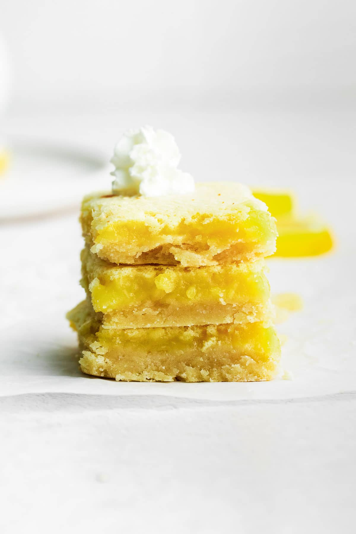Three Lemon Squares stacked on top of each other with glass of milk and baking dish in background