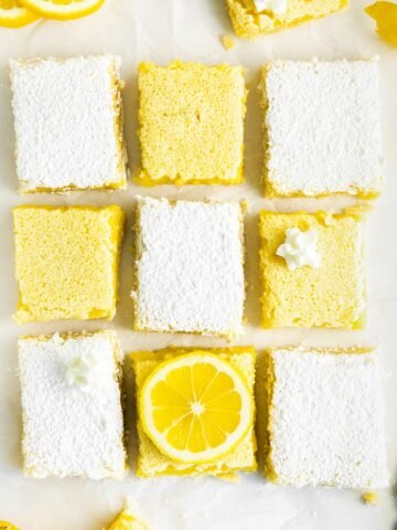 several lemon bars on white parchment paper, some topped with powdered sugar