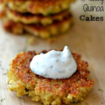 quinoa cake on a wood cutting board topped with a dollop of cucumber dill sauce