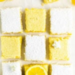 nine lemon bars on a white table some topped with powdered sugar