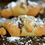 closeup of a crescent rolls covered with powdered sugar on a baking sheet