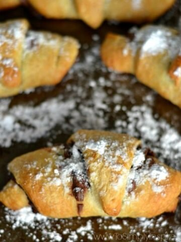 A close up of three crescent rolls sprinkled with powdered sugar on a baking sheet