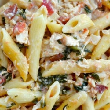 A close up of pasta with spinach, bacon and chicken