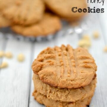 a stack of 3 peanut butter cookies with a plate in the background