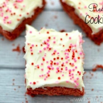 Three red velvet cake cookie bars topped with cream cheese frosting and sprinkles