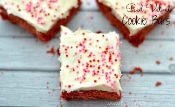 a closeup of three red velvet cake cookie bars topped with cream cheese frosting and sprinkles