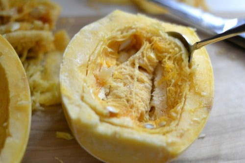 spaghetti squash with a spoon scooping out pulp