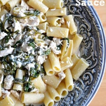 A big silver bowl with penne pasta topped with spinach and chicken mixture