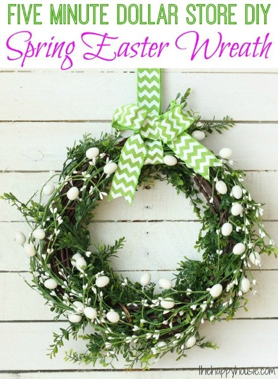 a green wreath with white easter eggs hung with a green and white ribbon