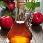 Apple cider vinegar in glass bottle and basket with fresh apples