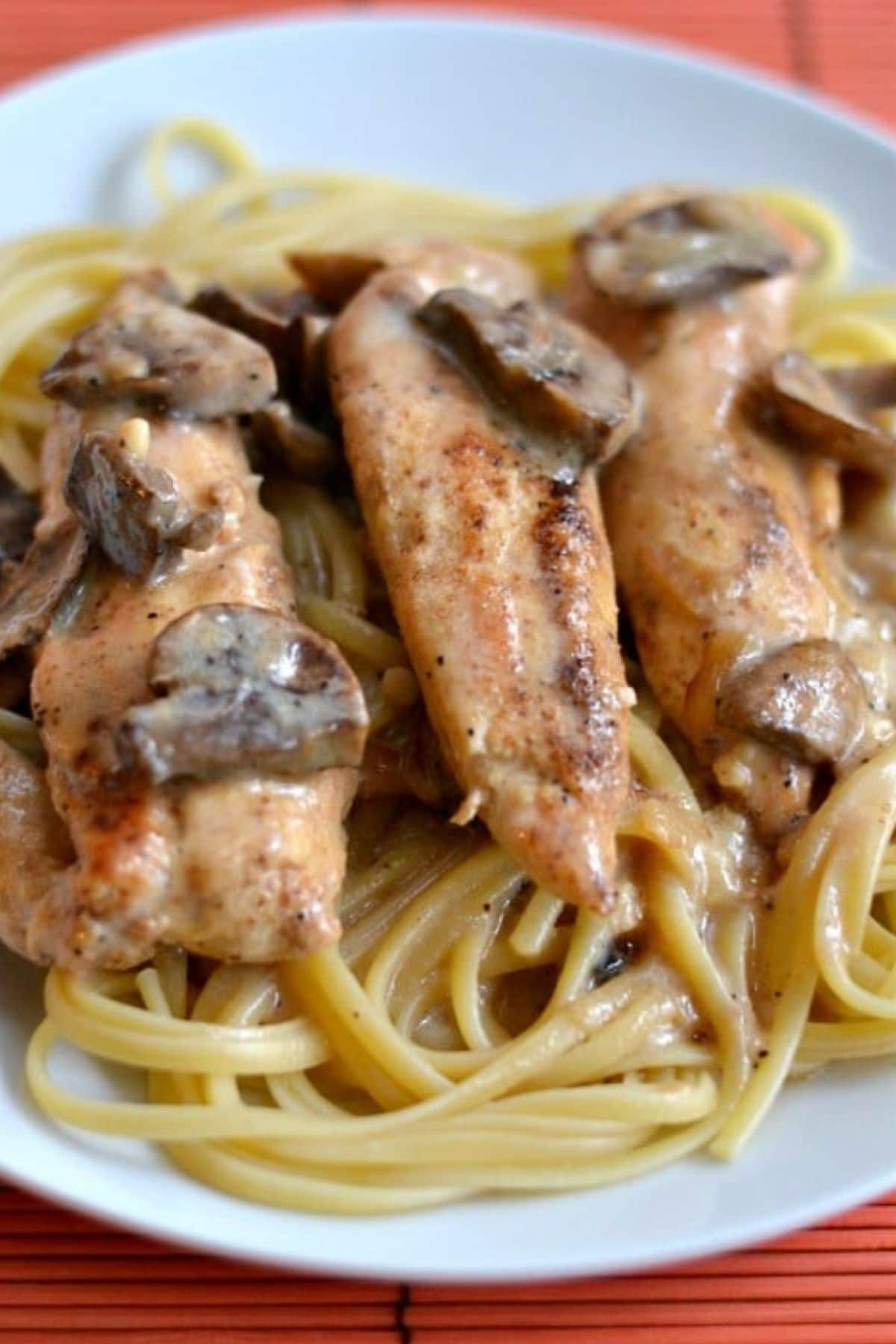 three chicken tenders in a mushroom sauce over spaghetti