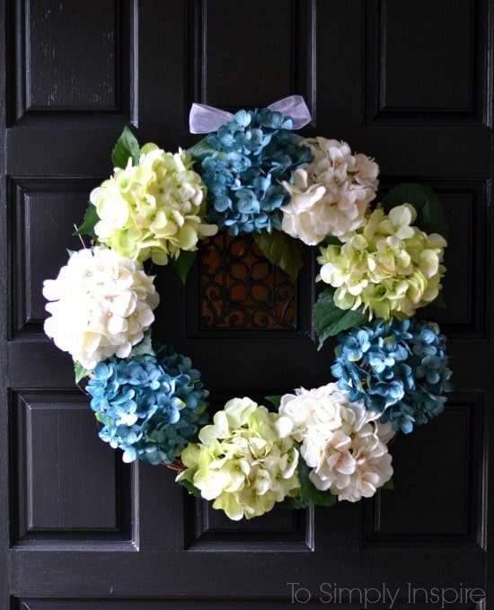DIY spring wreath with blue green and white hydrangeas on a black door