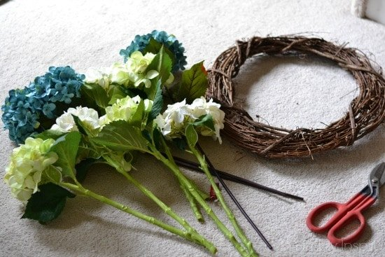 grapevine wreath and hydrangea flower stems on floor